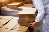 Close up of young female worker picking up stacks of folded cardboard boxes from a bigger stack in factory storage room. - 197927951