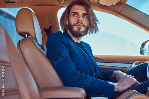 Foto op Plexiglas Kapsalon A handsome fashionable male with a beard and long hair sitting in a luxury car.
