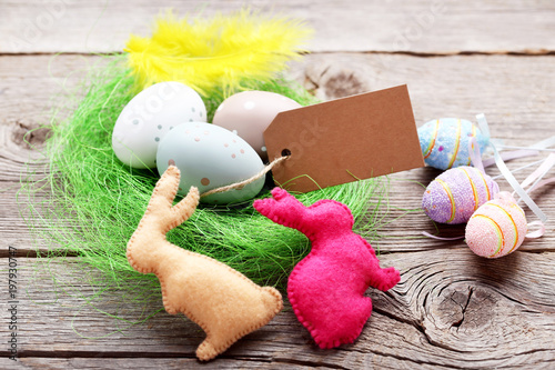 Blank card with painted eggs in green nest and fabric rabbits