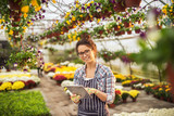 Beautiful cheerful smiling modern florist woman working on a tablet and looking at the camera while standing in the big colourful greenhouse. - 197934564