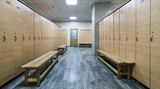 Wooden lockers with a wood bench in a locker room with doors closed. Locker room interior in modern fitness gym  - 197939310