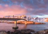 Beautiful bridge at sunrise in Lofoten islands, Norway. Landscape with bridge, colorful sky with pink clouds, snowy mountains, rocks, blue sea in the morning in winter. Travel in europe.Transportation