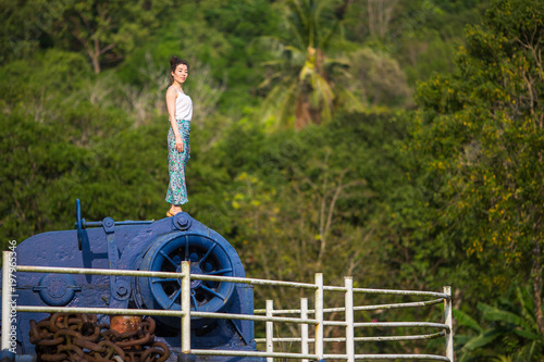 Young beautiful mixed race woman stands on the giant engine of an abandoned ship.
