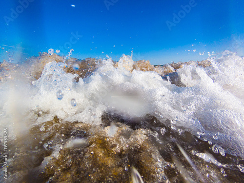 Foam on a crest of a sea wave against a blue sky. Sea waves roll on to shore. Sea foam. Stormy sea. Closeup
