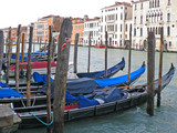 Venice. Italy. Large gondola boats are moored to the pier. On the other side of the canal are beautiful buildings.
