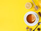 Flat lay on the yellow bright background Black tea Lemon Cinnamon Star Anise brown sugar jar of Honey Copy space