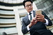 Low angle view of Asian businessman text messaging on smartphone in airport