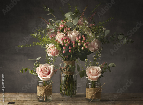 Foto Murales Bouquets of roses in jam jars on a rustic wooden table