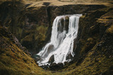 beautiful icelandic landscape with scenic Fagrifoss waterfall and rocks with green vegetation