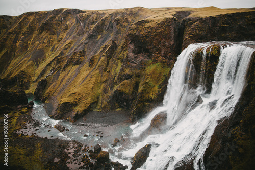scenic icelandic landscape with majestic Fagrifoss waterfall and rocks with green vegetation - 198001766