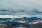 majestic icelandic landscape with mountains and steam from hot springs at cloudy day