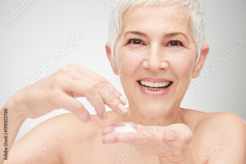 Foto Murales Head shot of beautiful senior woman putting on the cream.