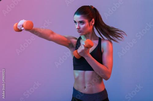 Poważna młoda sport kobieta robi ćwiczeniom z dumbbells
