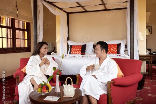 Happy couple in bathrobes enjoying breakfast in hotel bedroom during honeymoon Poster