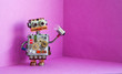 Robot electrician holds a light bulb in his hand. Creative design futuric robotic toy on pink background. Copy space