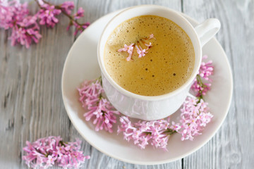 cup of coffee with spring flowers on the wooden background