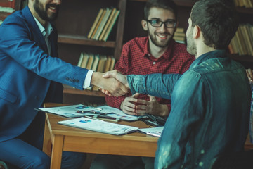business partners shake hands after discussing the contract at t