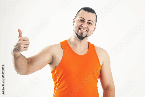 portrait of sporty guy - bodybuilder in jeans and an orange shir