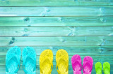 Colorful flip flops of a family of four on a turquoise wood planks background with copy space, family summer beach concept - 198031946