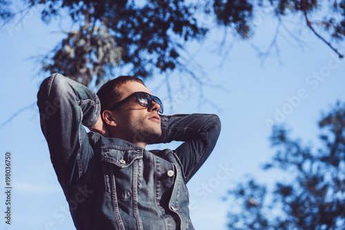 Man in sunglasses standing with hands by head on sky background