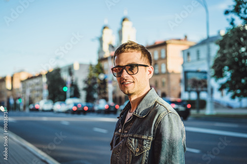 Foto Murales Stylish young man in sunglasses on city street