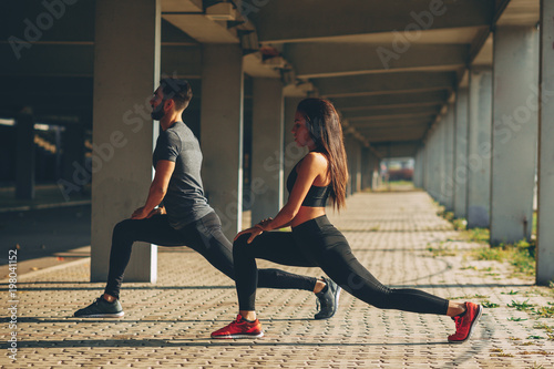 Young couple stretching legs in urban environment