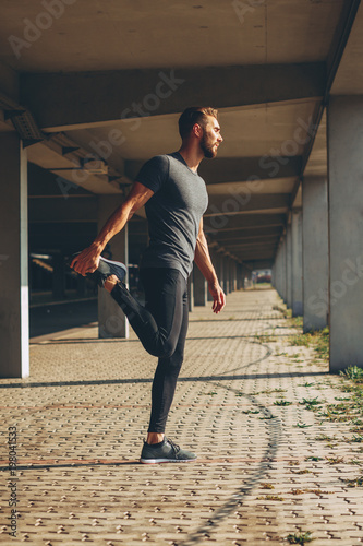 Young man stretching legs in urban environment