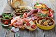 Leinwandbild Motiv Iberische Spezialitäten: Spanische Chorizo, Serrano-Schinken und  weitere Tapas  – Typical Iberian bar food: Spicy chorizo sausage, Serrano ham and other mixed tapas