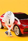Easter egg businessman standing near red car