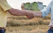 Two farmers shaking hands in field