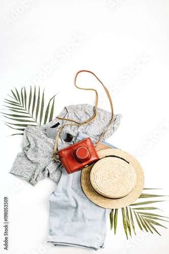 Woman fashion travel flatlay. Retro camera, straw, shorts, sunglasses and tropical palm leaf. Top view, flat lay.