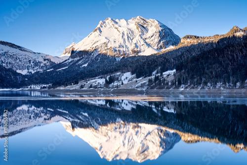 Foto op Aluminium Bergen Wägitalersee mit Spiegelung des schneebedeckten Fluebrig, Eisschicht, Winterlandschaft, Bergwald, Schatten, Sonne, blauer Himmel
