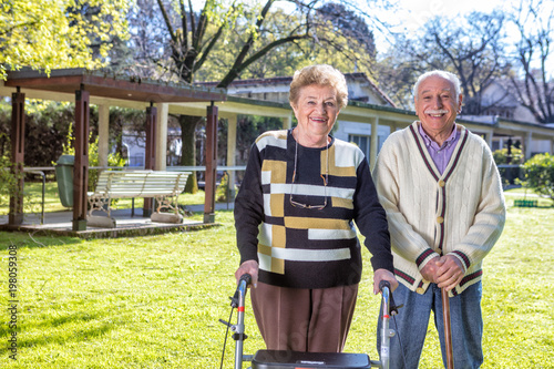 Elderly couple with crutches outdoor happy with life
