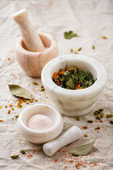 Spices and dry herbs in a marble mortars