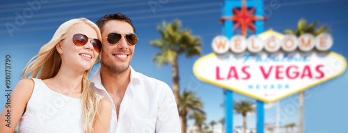 summer holidays, vacation, tourism and travel concept - happy couple in shades over welcome to fabulous las vegas sign background