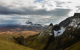 Dark rocks in the front and a snow covered mountain in the background of a mountain range in the Quiraing, Isle of Skye, Scotland