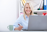 Attractive mature businesswoman working on laptop in her workplace - 198082944