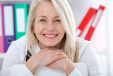 Lovely middle-aged blond woman with a beaming smile sitting at office looking at the camera - 198083109