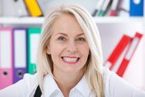 Lovely middle-aged blond woman with a beaming smile sitting at office looking at the camera - 198083118