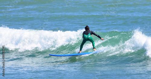 Fototapeta Surfer in wetsuit riding wave