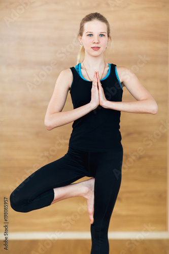 Young blonde Woman in a black suit working out indoors, doing yoga exercise on mat, standing in Vrksasana Posture, Tree Pose, full length.