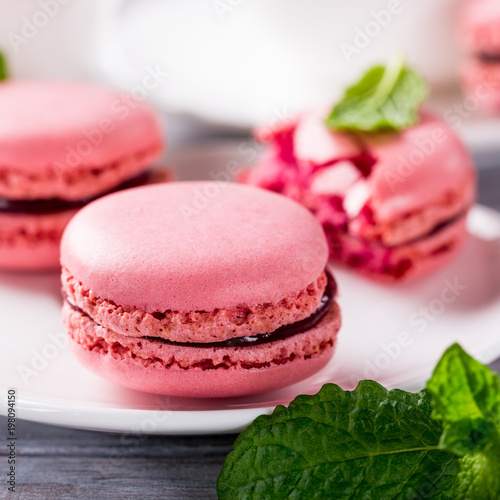 Plexiglas Macarons French raspberry macaroons with mint leaves on old white wooden background. Holidays food concept.