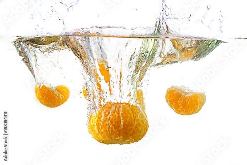 Fresh mandarin falling in water splash, isolated on white.