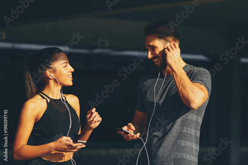 Young sports couple listening to music and laughing
