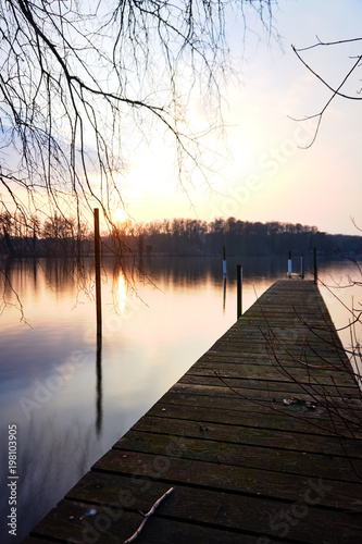 Plexiglas Pier landing stage above glassy water at sunset
