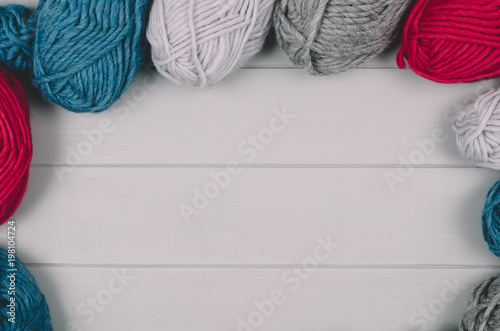 Knitting accessories assortment background with wool on gray wooden table. Photograph taken from above top view. Frame composition with copy space around products.