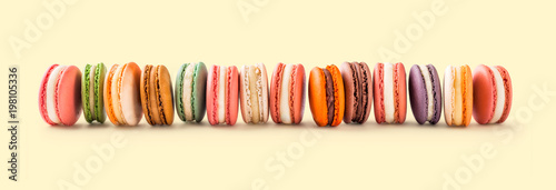 Fotobehang Macarons French macarons large arrangement lined up on light yellow background in studio