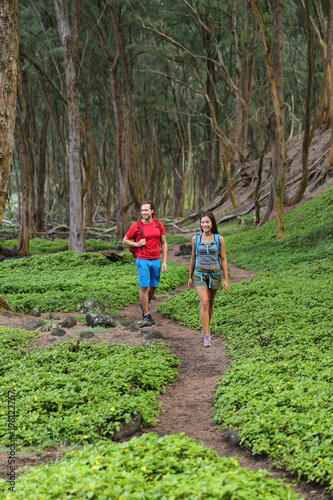 Outdoor nature people walking in forest hiking on trail path in Hawaii mountains rainforest. Happy couple with backpacks going camping with bags, enjoying landscape. Tourists on tropical travel.