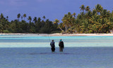 Fly-fisherman and guide walking on flats in turquoise waters in French Polynesia - 198133397