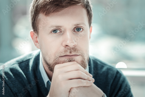 Me alone. Thoughtful handsome beardful man supporting chin by hands looking straight being in the empty room.